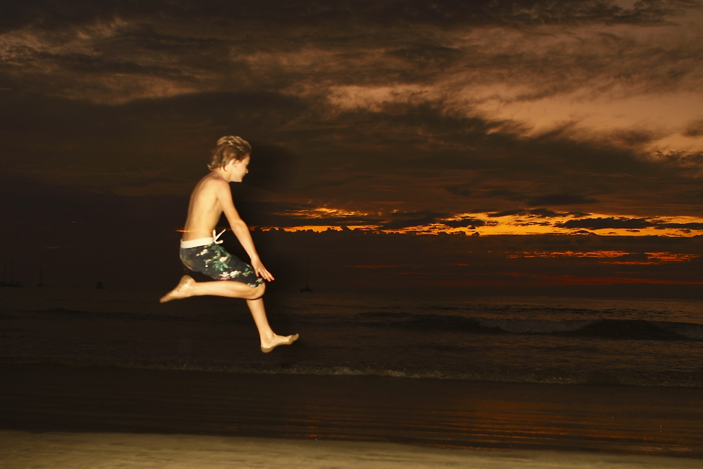 costa rica ocean sunset boy jumping beach